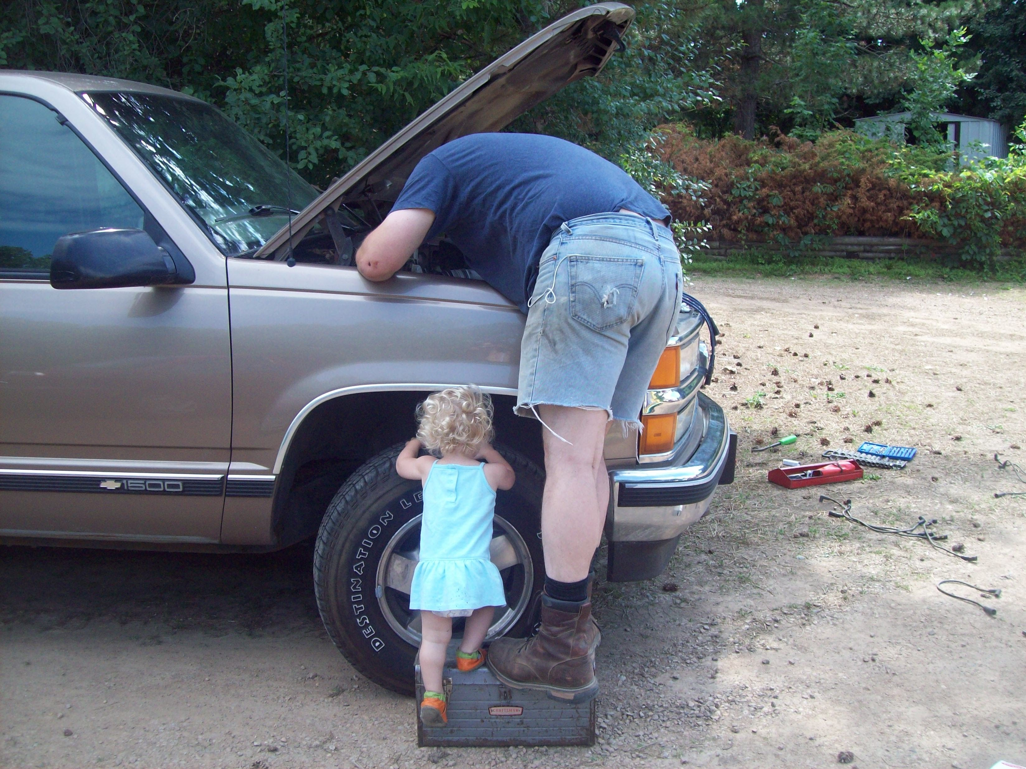 Child and parent working on a truck together.